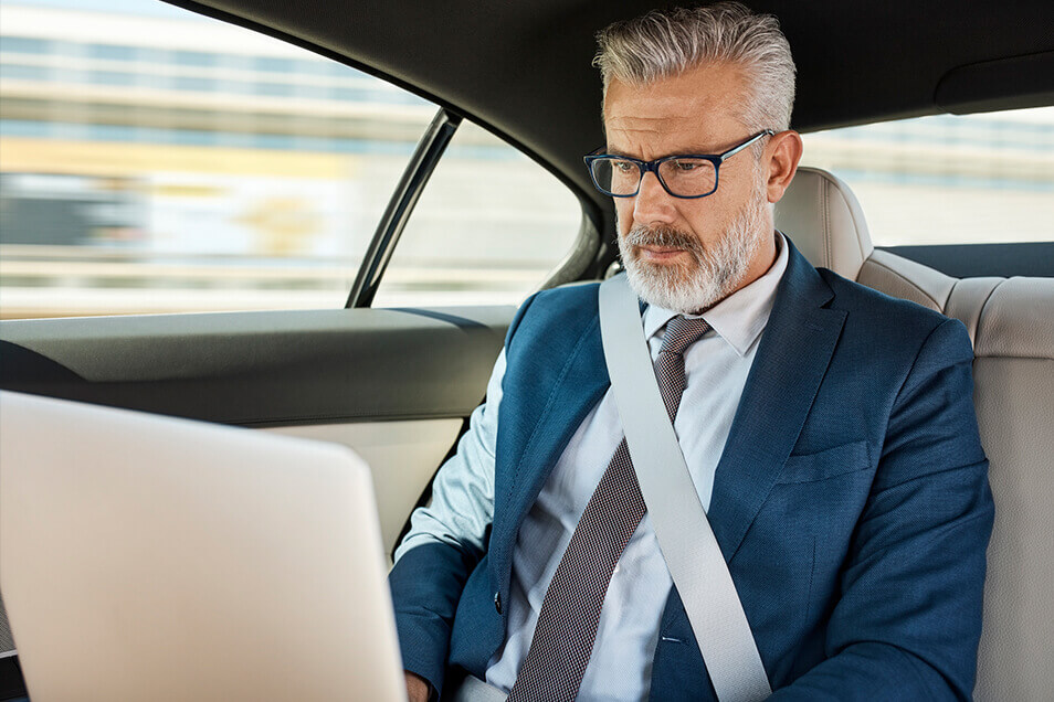 Man working on computer in car