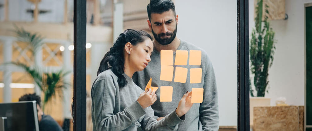 man and woman using post it notes on window