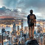 Man standing on rock overlooking city