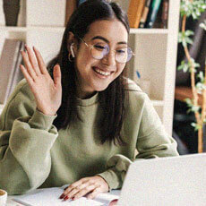 happy woman raising her hand and looking at laptop