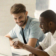two men looking at laptop