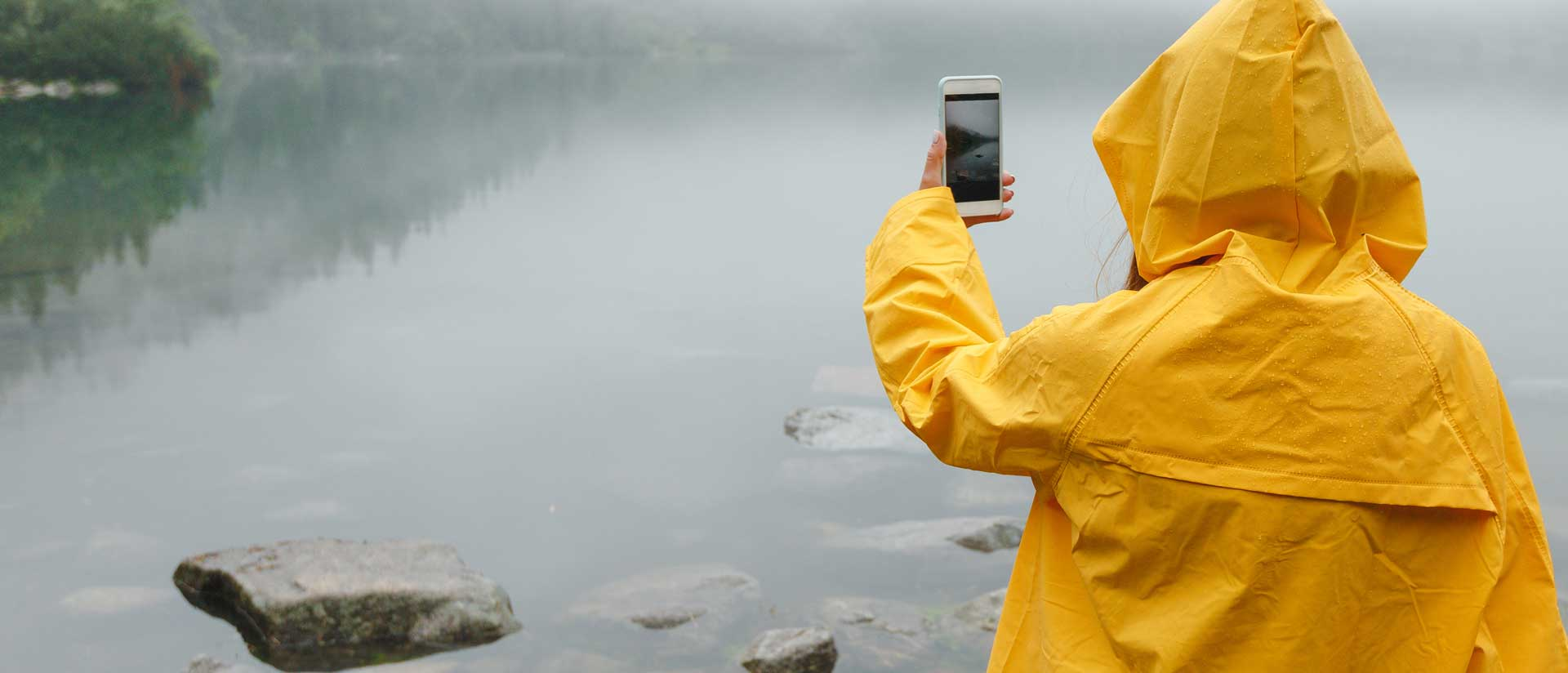 person in raincoat taking a photo with mobile phone