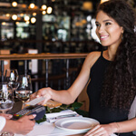 woman using contactless payment at fancy restaurant