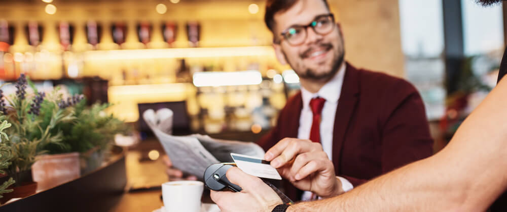 man using contactless payment with card at restaurant