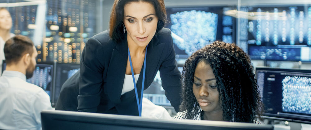 two women in server room looking at laptop
