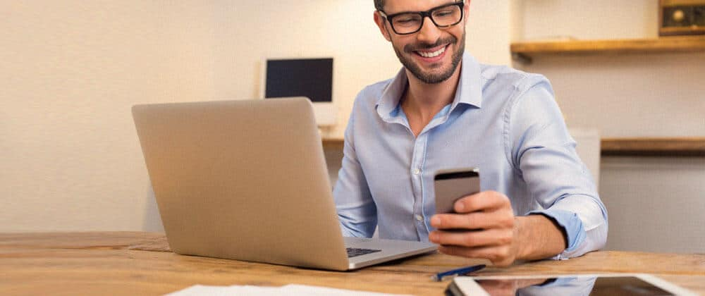 man at desk holding phone and looking at laptop